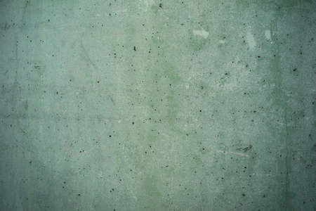 damaged green concrete background texture with small holes and scratches