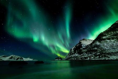 Hermosa aurora boreal verde en la playa de Haukland en las islas Lofoten en Noruega