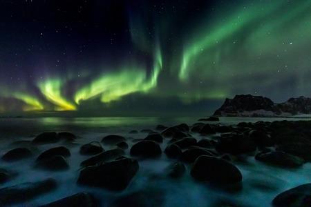 Bellissima aurora boreale verde sulla spiaggia di Utakleiv sulle isole Lofoten in Norvegia Archivio Fotografico