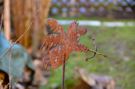 A figure of a rusty angel with a bow.