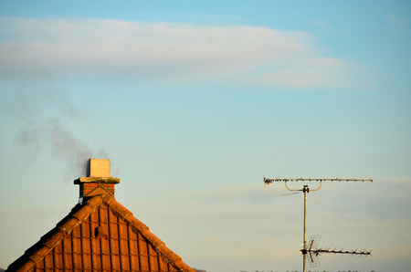 Smoke out of a chimney on top of a roof with a radio mast next to it.