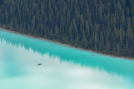 Canoes at Lake Louise from above on glacier blue water with forest.