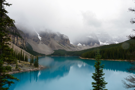 Glacier blue water of the Morain Lake with trees and mountains.