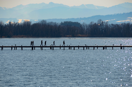 People walk at boardwalk on lake with mountains landscape background