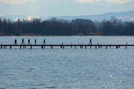 Holzsteg und Promenade am See mit Berglandschaft und Menschen