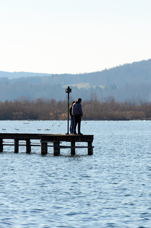 Two man standing on a boardwalk at a lake and watching the nature landscape