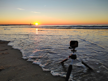 A action camera on tripod with wave on the sand beach during sunset in The Hague Banque d'images
