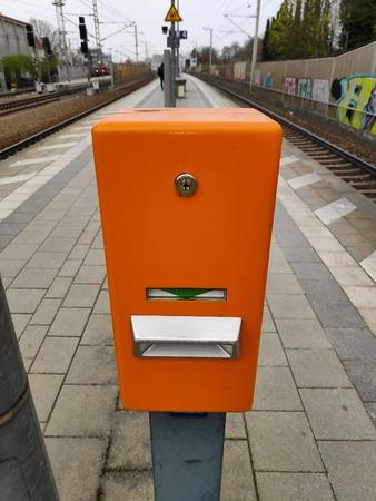 Ein deutscher orangefarbener Bahnhofs-Zugscheinentwerter mit grünem Pfeil