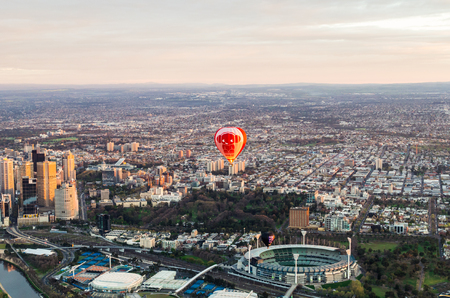 Melbourne, Australia - September 15, 2013: aerial view of a hot air balloon floating over the MCG and Melbourne sporting precinct at dawn.