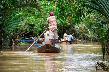 베트남의 메콩 델타에있는 칸토 (Can Tho) 지방의 운하에있는 전통 카누. 스톡 콘텐츠