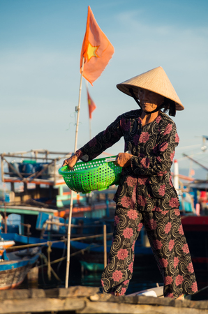 carrying: Duy Hai, Vietnam - August 15, 2015: women bringing in the nights catch in Duy Hai, a fishing village across the Thu Bon River from Hoi An.
