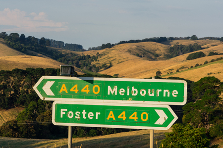 Signs on the South Gippsland Highway pointing towards Foster and Melbourne, among the rolling hills of South Gippsland. Фото со стока