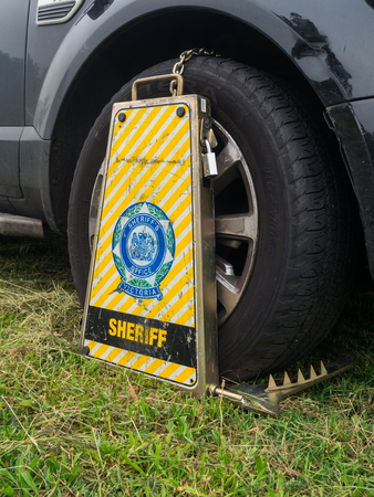 Melbourne, Australia - November 12, 2015: a car wheel-clamped by the Victorian Sheriffs Office. The Sheriff takes action against people who do not comply with debt-related court orders.
