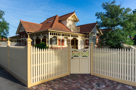 Melbourne, Australia - February 17, 2018: a brick heritage home with a white wooden picket fence in suburban Caulfield in the City of Glen Eira.