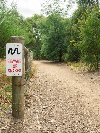 A snake warning sign by a dirt path along the banks of the Yarra River in Richmond, Melbourne, Australia