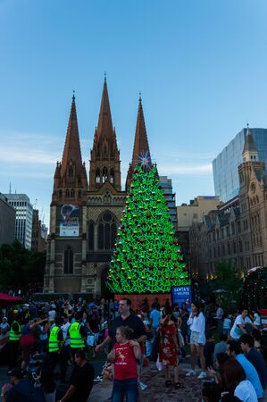 Melbourne, Australia - December 22, 2017: illuminated Christmas tree in Federation Square, a large public space in Melbourne. St Paul's Anglican Cathedral is in the background.