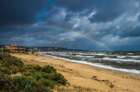 Rainbow over Frankston pier in the southern suburbs of Melbourne, Australia on a windy winter day. Stok Fotoğraf