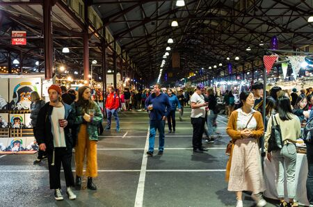 Melbourne, Australia - March 6, 2019: visitors in a market shed at the Queen Victoria Night Market, a weekly food and craft market during summer at the Queen Victoria Market. Editorial