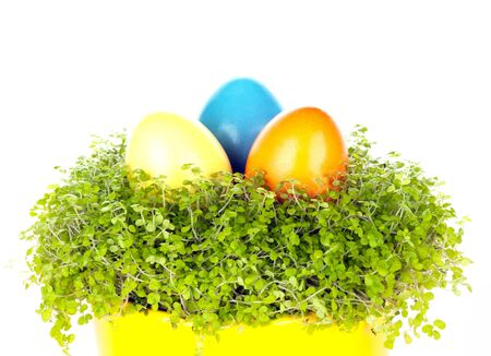 Three different coloured eastrn eggs in a yellow cup photo