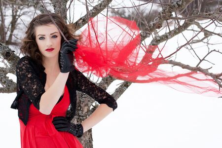 Beautiful woman with dark hair and red lips in white snow photo
