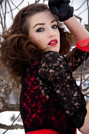beautiful young woman outside in winter with dark hair and red lips photo