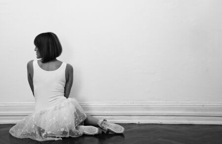 beautiful ballerina is sitting on the floor in black and white photo