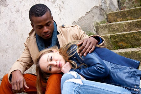 woman in white: young happy couple is sitting outside ethnicity Stock Photo