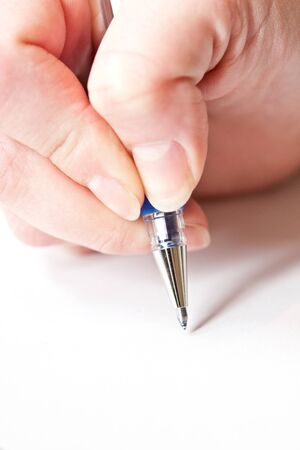 womans hand is writing a letter with a pen  photo