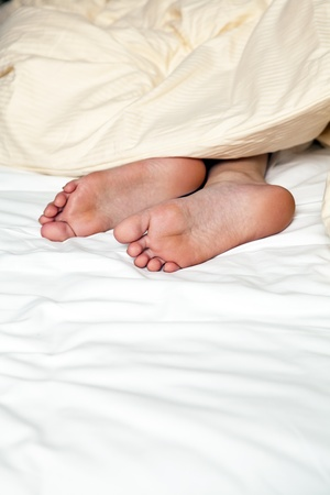 nude feets looking out of blanket in bed photo