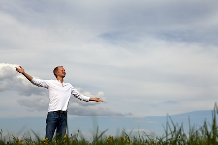 man is standing outside in spring with arms wide open and breathing