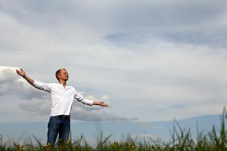 Mann steht draußen im Frühjahr mit weit offenen Armen und Atmung