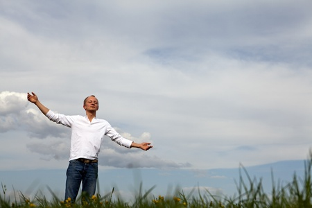 arms wide open: man is standing outside in spring with arms wide open and breathing