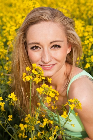 young beautiful blonde girl in a field in summer happy photo