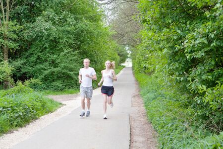 young couple is jogging in the forest photo