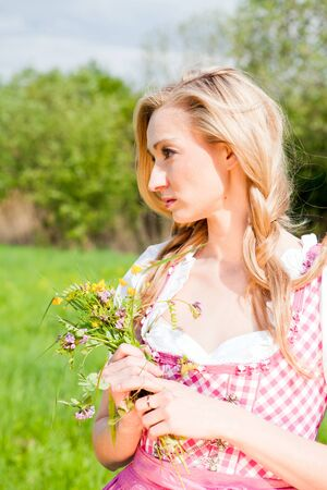 young woman with pink dirndl outdoor in summer photo