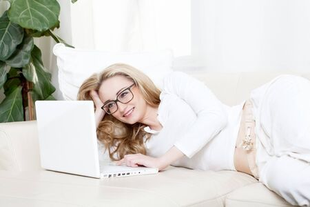 young blonde woman on couch with notebook Stock Photo - 13612522