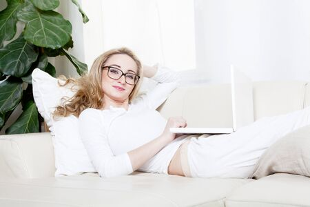 young blonde woman on couch with notebook Stock Photo - 13612546