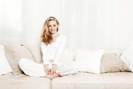 beautiful blond woman sitting on couch Stock Photo - 13612530