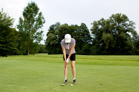 woman is playing golf on course  in summer in a golf-club photo