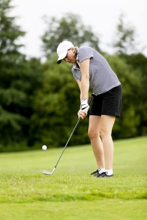 Frau spielt Golf auf Kurs im Sommer in einem Golf-Club