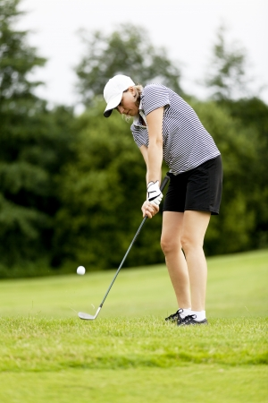 woman is playing golf on course in summer in a golf-club