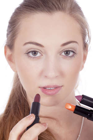 young beautiful woman applying colored lipstick on lips isolated photo