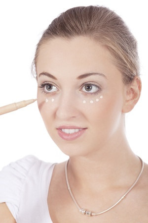 young beautiful woman applying concealer on face isolated photo