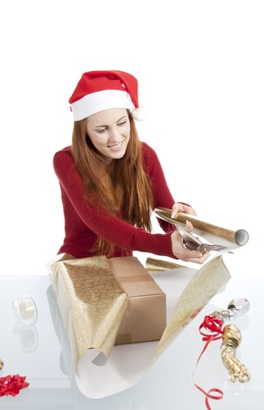 young woman is packing  present for christmas isolated on white photo