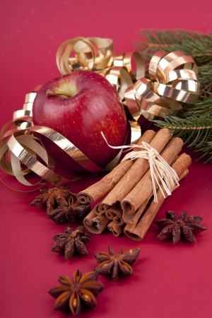 christmas decoration aromatic red apple, cinnamon, anise and tree on red background photo