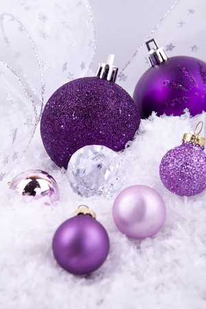 beautiful christmas decoration in purple and silver on white snow sparkle photo