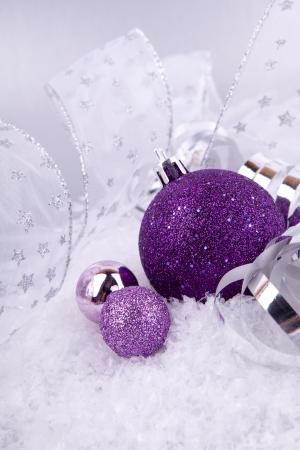 Schöne Weihnachts-Dekoration in Purpur und Silber auf weißem Schnee funkeln