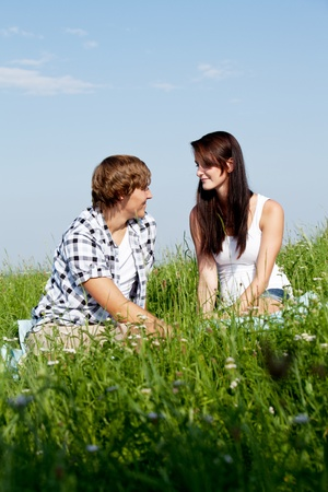 young couple outdoor in summer on blanket in love photo