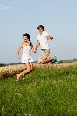 young happy couple jumping outside in summer on field  photo
