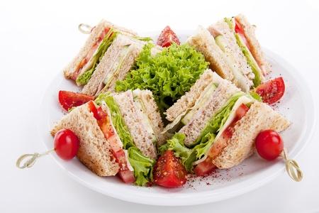 sandwich de pollo: bocadillo dulce del club sabrosos quesos con jam�n lechuga y pan tostado aislados en fondo blanco Foto de archivo